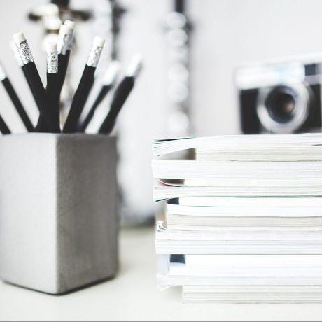 Diese Abbildung zeigt eine Kamera, Stifte in einem Behälter und Zeitschriften.